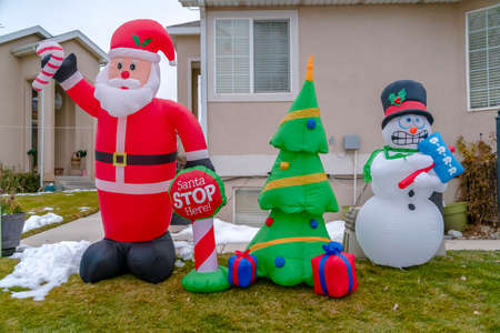 Inflatable Christmas decorations on a grassy yard with snow in winter 免版税图像