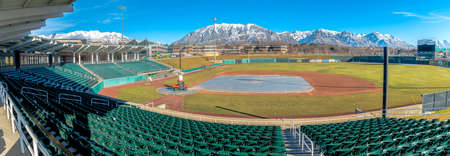 Baseball field with green tiered seating against mountain and vibrant blue sky