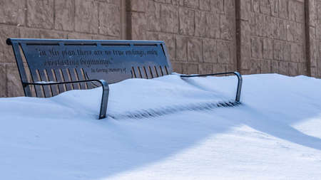 Panorama Metal bench with the seat covered in powdery white snow on a sunny winter day