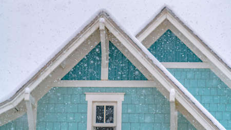 Clear Panorama Snow falling on a blue home in Daybreak Utah with cloudy sky in the background Stock Photo