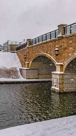 Vertical Bridge over the rippling water of Oquirrh Lake with snowy white shore