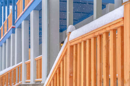 Winter view of the stairs leading to the front porch of a home with balcony