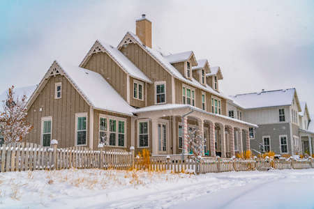 Winter scene with cozy homes and wooden fences under a cloudy sky in Daybreak