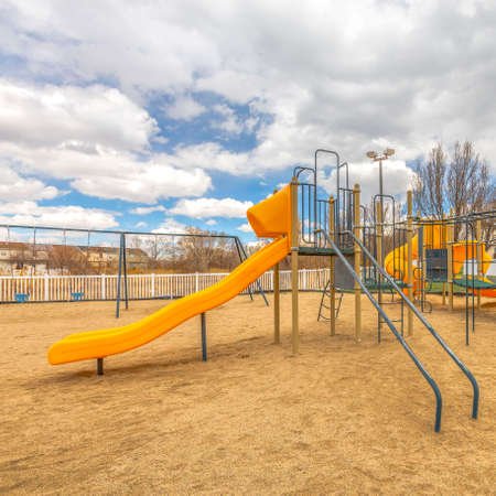 Square Playground with slides and swings under the blue sky filled with puffy clouds Reklamní fotografie