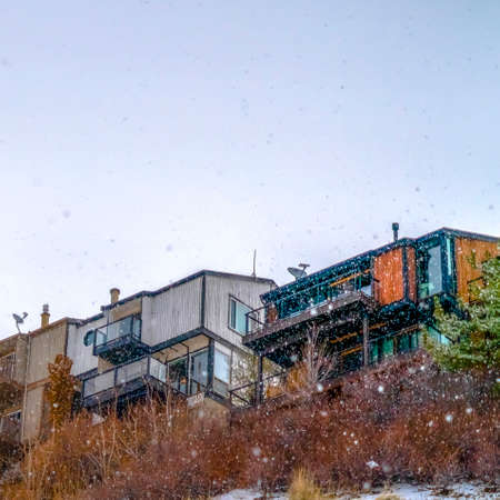Square Homes on snowy mountain against bright sky Imagens