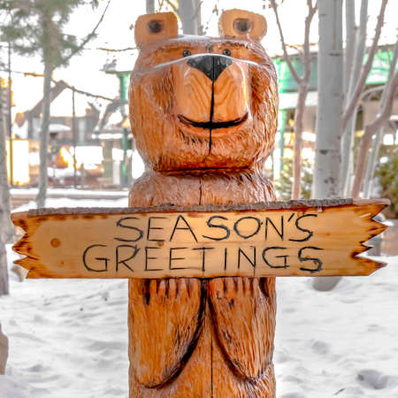 Square Bear wood sculpture on a landscape covered with powdery white snow in winter