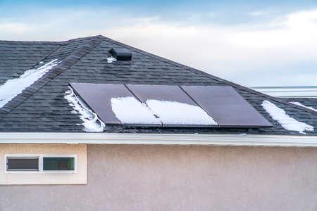 Panneaux solaires sur le toit d'une maison contre le ciel bleu avec des nuages