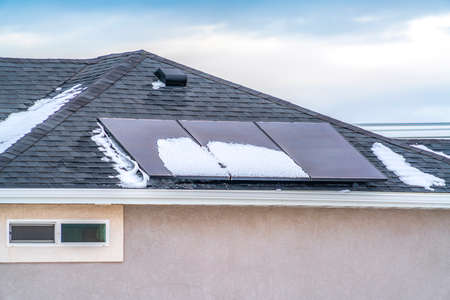 Solar panels on the roof of a home against blue sky with clouds