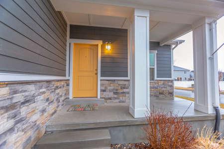 Entrada de una casa con escaleras que suben al porche delantero y a la puerta.