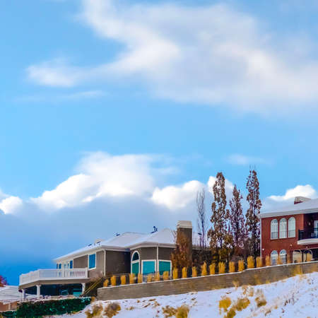 Square Homes on snowy hill against sky with puffy clouds