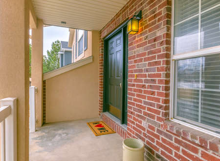 Facade of a home with a small porch and classic red brick wall. A welcoming doormat and wall lamp can be seen by the green front door.