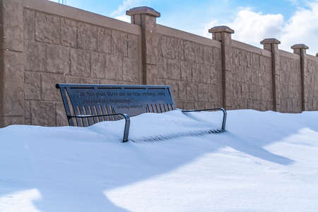 Metal bench with the seat covered in powdery white snow on a sunny winter day. The outdoor bench is placed against a concrete fence with a cloudy sky overhead. Фото со стока
