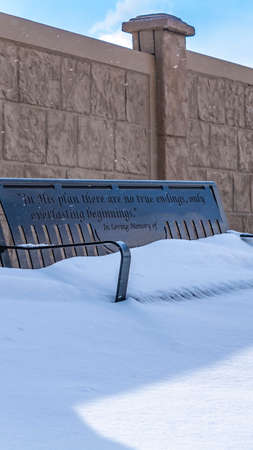 Clear Vertical Metal bench with the seat covered in powdery white snow on a sunny winter day. The outdoor bench is placed against a concrete fence with a cloudy sky overhead.