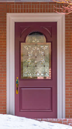 Clear Vertical Entrance of a home with a beautiful front door and snowy yard in winter. The door with a decorative glass panel is between lamps mounted on the exterior red brick wall. Stock Photo