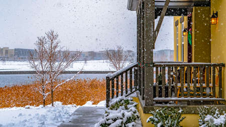 Panorama Entrance of a home in Daybreak Utah with lake and buildings in the background. The path on the snowy yard leads to the stairs and porch of the house. Stock Photo