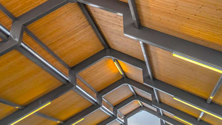 Panorama Close up of the brown wooden roof of a pavilion in Eagle Mountain Utah. Bright retangular lights installed on the gray frames illumintaes the interior of the building. Imagens