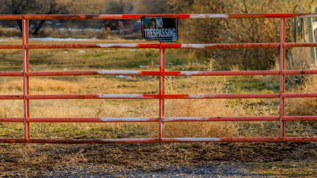 Clear Panorama No Trespassing sign on the gate of a private property viewed on a sunny day. A grassy terrain with trees against cloudy sky can be seen behind the weathered red gate. Banque d'images - 122762093