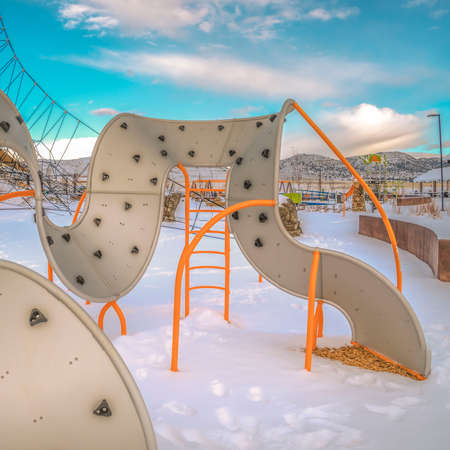 Clear Square Climbing frames on a playground with the ground covered with snow in winter. Striking snow capped mountain against peaceful blue sky can be seen in the distance.