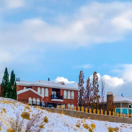 Clear Square Homes on snowy hill against sky with puffy clouds. Scenic snow covered landscape in Salt Lake City during winter season. Lovely homes sits on top of a snowy hill against blue sky with puffy clouds.
