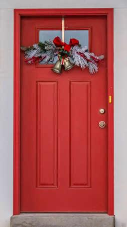Puerta frontal vertical con panel de vidrio y decoración navideña contra una pared blanca estriada. Plantas en macetas de colores adornan las escaleras exteriores que conducen a la puerta roja. Foto de archivo
