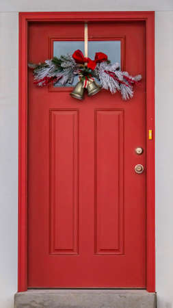 Vertical Front door with glass panel and holiday decoration against a ribbed white wall. Plants on colorful pots adorn the outdoor stairs that leads to the red door. Stock Photo