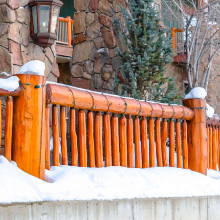 Clear Square Building in Park City Utah with wooden railings and mosaic stone wall. Powdery white snow can also be seen in the landscape during winter season.