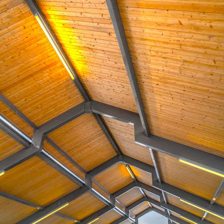 Close up of the brown wooden roof of a pavilion in Eagle Mountain Utah. Bright retangular lights installed on the gray frames illumintaes the interior of the building. Imagens