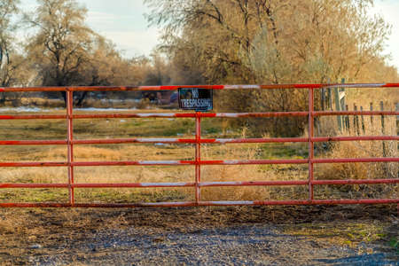 No Trespassing sign on the gate of a private property viewed on a sunny day. A grassy terrain with trees against cloudy sky can be seen behind the weathered red gate. Banque d'images - 122762660