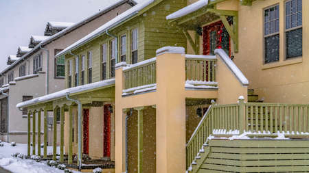 Clear Panorama Pathway in front of cozy homes in Daybreak Utah viewed in winter. The snow falling from the cloudy sky creates a blanket of frost on the landscape. Stock Photo