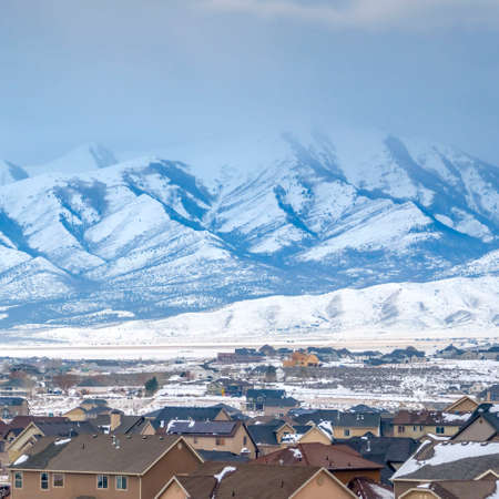 Clear Square Homes with a snowy mountain and cloudy sky background viewed in winter. The scenic town is coated with fresh powdery snow on this frosty season.