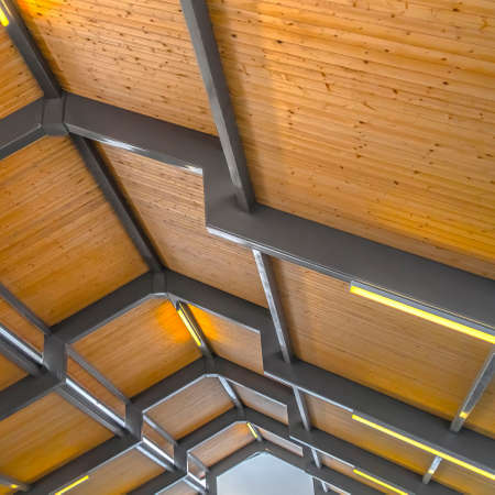 Square Close up of the brown wooden roof of a pavilion in Eagle Mountain Utah. Bright retangular lights installed on the gray frames illumintaes the interior of the building.