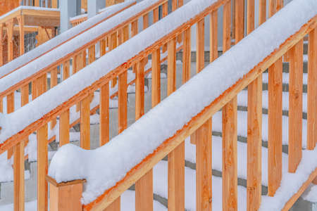 Close up of the outdoor stairs of a home in Daybreak Utah during winter. The wooden treads and handrails of the stairs are covered with icy snow.