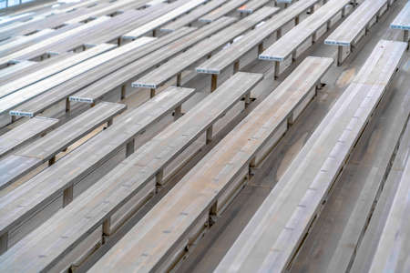 Close up of tiered rows of benches at a sports field viewed on a sunny day. Seating numbers can be seen on the surface of the raised bleachers. Stock Photo