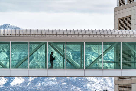 Skyway connecting buildings with a snowy mountain and cloudy sky background. Silhouette of a man walking inside the passage ay can be seen through the clear glass wall.