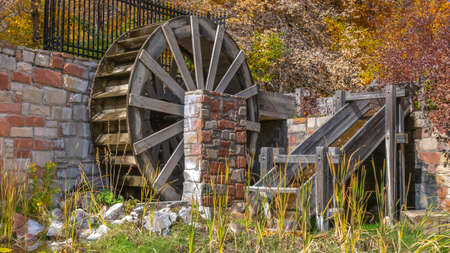 Wooden water wheel and flume at a grassy pond viewed on a sunny day. Lush autumn foliage can be seen over the stone brick wall in the background. Stockfoto - 122763247