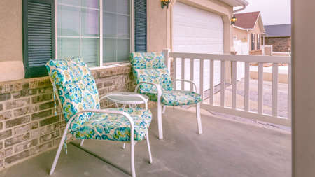 Clear Panorama Facade of a home with a view of the green front door and white garage door. On the porch are table and colorful chairs in front of the window.