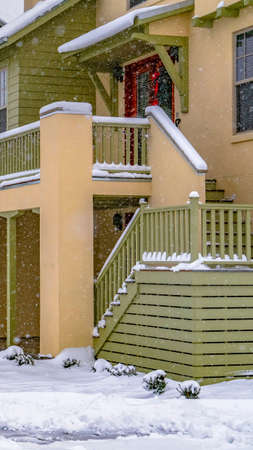 Vertical Pathway in front of cozy homes in Daybreak Utah viewed in winter. The snow falling from the cloudy sky creates a blanket of frost on the landscape.