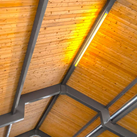 Clear Square Close up of the brown wooden roof of a pavilion in Eagle Mountain Utah. Bright retangular lights installed on the gray frames illumintaes the interior of the building.