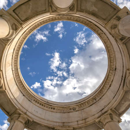 Clear Square Circular structure supported by huge columns viewed on a sunny day. A beautiful and vast blue sky with puffy clouds can be seen over the structure.