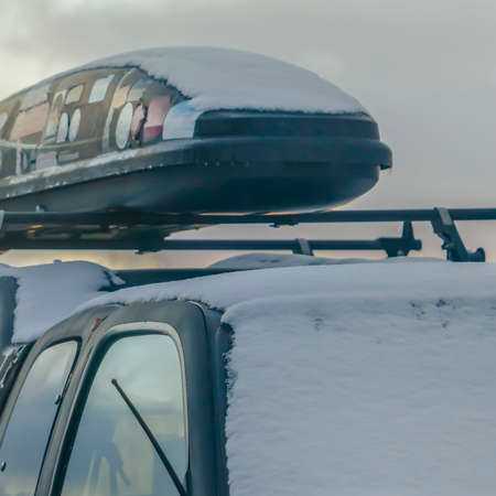Clear Square Black vehicle with roof rack and car top carrier covered with snow in winter. A cloudy sky with a golden glow can be seen in the background at sunset.
