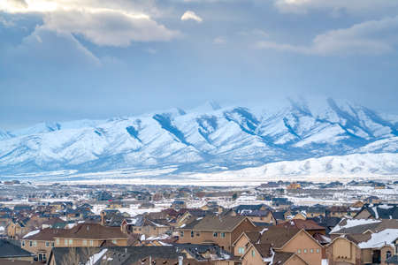 Homes with a snowy mountain and cloudy sky background viewed in winter. The scenic town is coated with fresh powdery snow on this frosty season.