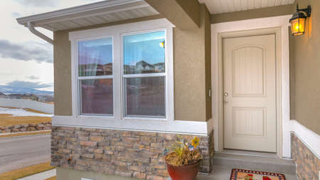 Panorama White front door and reflective window of a home against road and cloudy sky. A colorful doormat, potted plant, and wall lamp adorns this homes entryway.