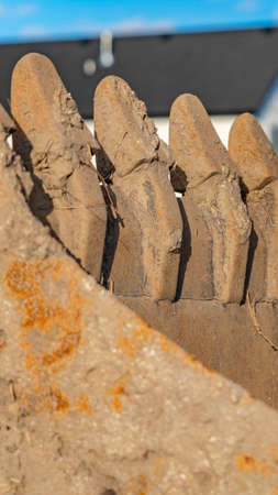 Vertical Dirty and rusty metal bucket teeth of an excavator viewed on a sunny day. Row of houses, mountain, and blue sky can be seen in the blurry background.