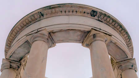 Clear Panorama Looking up at a white circular structure supported by smooth columns. A vast white sky can be seen behind the structure on this sunny day.