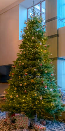 Vertical Traditional Christmas tree decorated with baubles lights and gift boxes. An alcove window seat behind the tree has a beautiful view of the sunny outdoors.