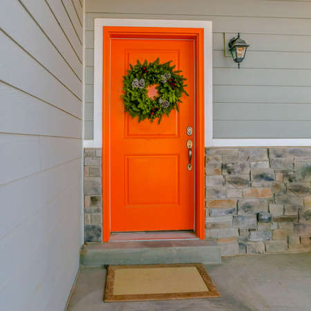 Clear Square Home with a welcoming wreath hanging on the orange front door. A simple doormat, green chair, and wall lamp can also be seen on theis home's entrance.