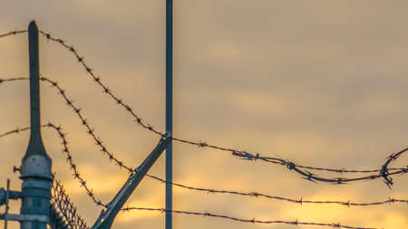 Panorama Chain link fence with barbed wire securing a Power Plant in Utah Valley. A towering light post can also be seen against the cloudy sky with a golden glow at sunset. Banco de Imagens