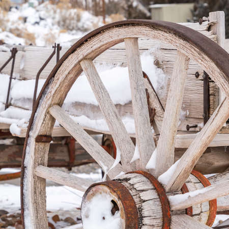 Clear Square Close up of the wheel of an old wooden cart against a snowy landscape in winter. The metal components of the cart and wheel is damaged with rust.
