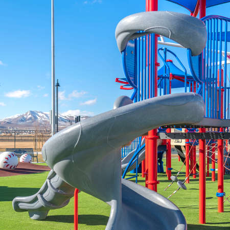 Square Spiral slide on a colorful playground against a vibrant lawn on a sunny day. The play area has a scenic view of snow capped mountain and vast sky in the distance.