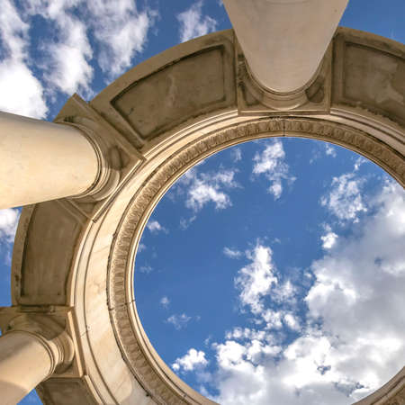 Square Circular structure supported by huge columns viewed on a sunny day. A beautiful and vast blue sky with puffy clouds can be seen over the structure. Stock Photo - 122763957